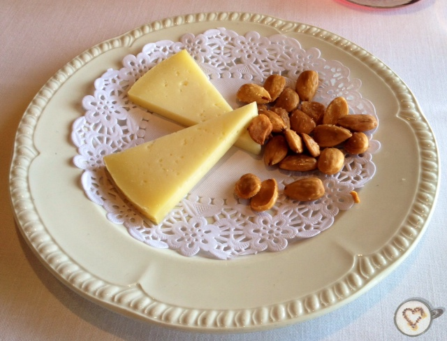 Queso manchego con almendras tostadas. Regalo de la casa. Manchego cheese with toasted almonds. Gift of the house. Manchego-Käse mit gerösteten Mandeln. Geschenk des Hauses.